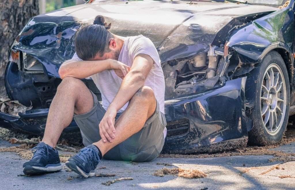 man in front of a wrecked car
