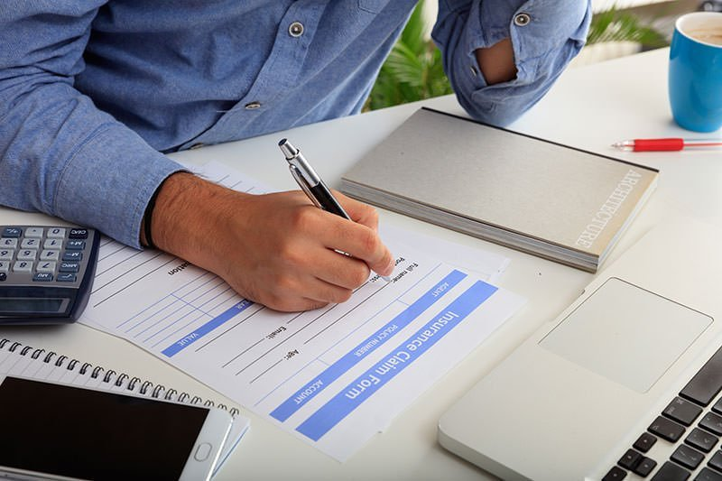 Man filling out insurance paper for lost wages